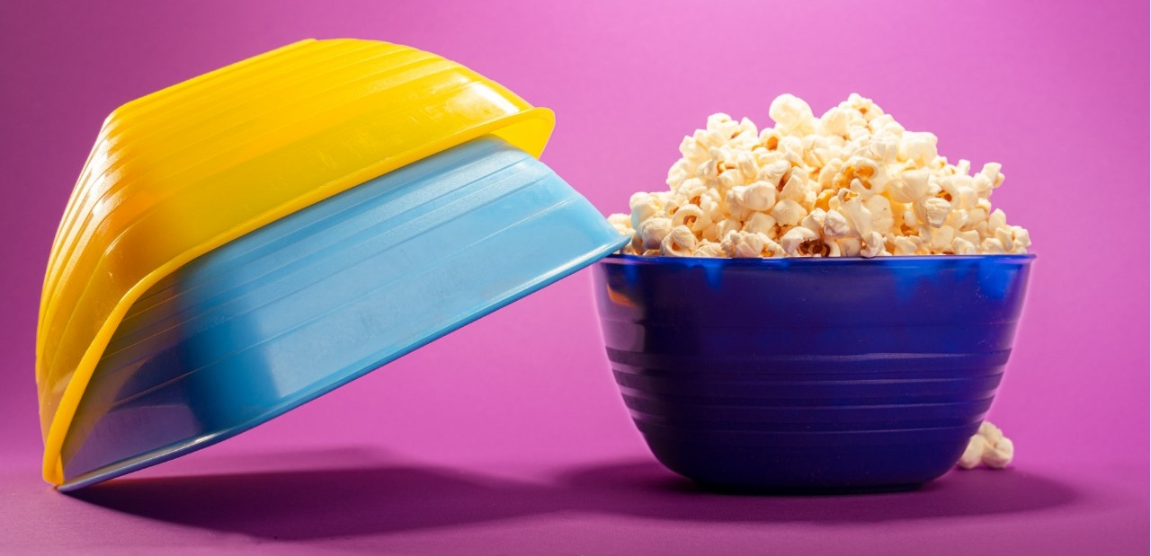"alt=""small colored bowls set with one filled with popcorn"""